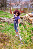 Young lady with rake spring cleaning the garden — Stock Photo