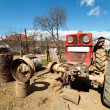 Beaten up old tractor in the countryside, on a jack — Stock Photo #5488824