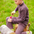 Boy sculpting in a log with a chisel - ストック写真