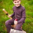 Boy sculpting in a log with a chisel — Stok fotoğraf