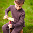 Stock Photo: Boy sculpting in log with chisel
