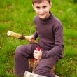Boy sculpting in a log with a chisel — Stock Photo #5519494
