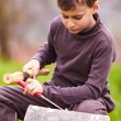 Boy sculpting in a log with a chisel — Stock Photo #5519495