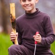Boy sculpting in a log with a chisel — Stock Photo #5519496