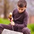 Boy sculpting in a log with a chisel — Stock Photo #5519499