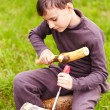 Boy sculpting in a log with a chisel - Stok fotoğraf