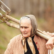 Senior farmer woman with a fork — Stock Photo