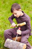 Boy sculpting in a log with a chisel — Stock Photo