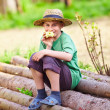 Royalty-Free Stock Photo: Happy boy outdoor sitting on pine logs