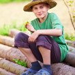 Happy boy outdoor sitting on pine logs — Stock Photo #5591392