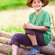 Happy boy outdoor sitting on pine logs — Stock Photo #5591395