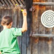Boy playing darts outdoor - Stock Photo