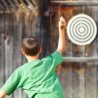 Stock Photo: Boy playing darts outdoor