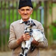 Old farmer with a baby goat - Stock Photo
