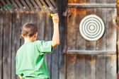 Boy playing darts outdoor — Stock Photo