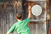 Boy playing darts outdoor — Stock Photo