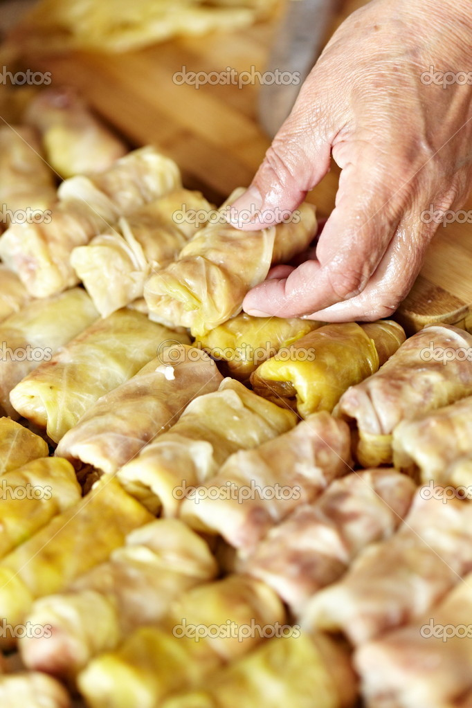 Cooking sarmale, a traditional Romanian dish, with grinded meat and rice wrapped in boiled cabbage leaves — Stock Photo #5599817