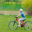 Boy with hat riding a bicycle — Stockfoto