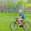 Boy with hat riding a bicycle — Foto Stock