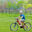 Boy with hat riding a bicycle — ストック写真