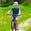 Boy with hat riding a bicycle - Stockfoto