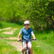 Boy with hat riding a bicycle — Stok fotoğraf