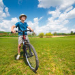 Boy with hat riding a bicycle — Stock Photo