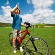 Boy on a bicycle drinking water — Foto Stock