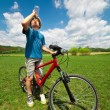 Boy on a bicycle drinking water — Stock Photo