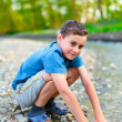 Happy child playing on a river bank — Stok fotoğraf