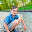Happy child playing on a river bank — Stock Photo