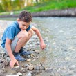 Child playing on a river bank - Stock Photo