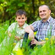 Stock Photo: Father and son sitting in grass