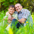 Father and son sitting in grass — Stok fotoğraf #5686353