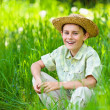 Happy boy sitting in grass — Stock Photo #5686355