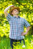 Young man in straw hat outdoor in a garden — Stock Photo
