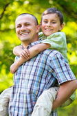 Father carrying son on his back — Stock Photo