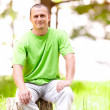 Young man sitting on a log — Stock Photo