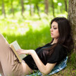 Beautiful girl reading a book outdoor — Stock Photo #5748524