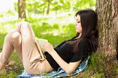 Beautiful girl reading a book outdoor — Stock Photo