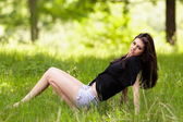Young woman sitting in grass — Stock Photo