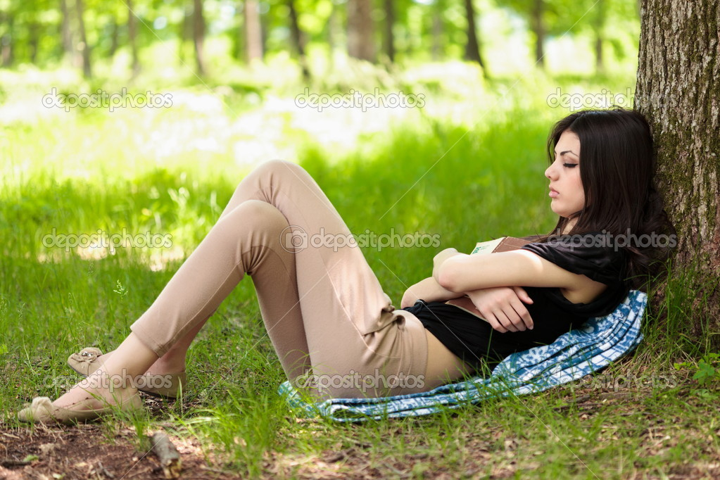 Young woman asleep in the forest, holding a book she just read — Stock Photo #5748527