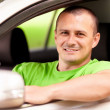 Young man driving new car - Stock Photo