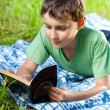 Child reading a book outdoor — Stock Photo