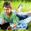 Boy reading a book outdoor — Stock Photo #5798604