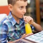 Child drinking orange juice — Stock Photo #5859681