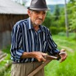 Old rural man sharpening scythe — Stock Photo #5859698