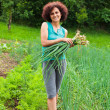 Young woman with a sheaf of young onions — Stock Photo