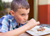 Chlapec jíst v restauraci — Stock fotografie