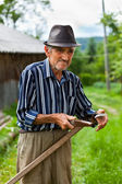 Old rural man sharpening scythe — Stock Photo